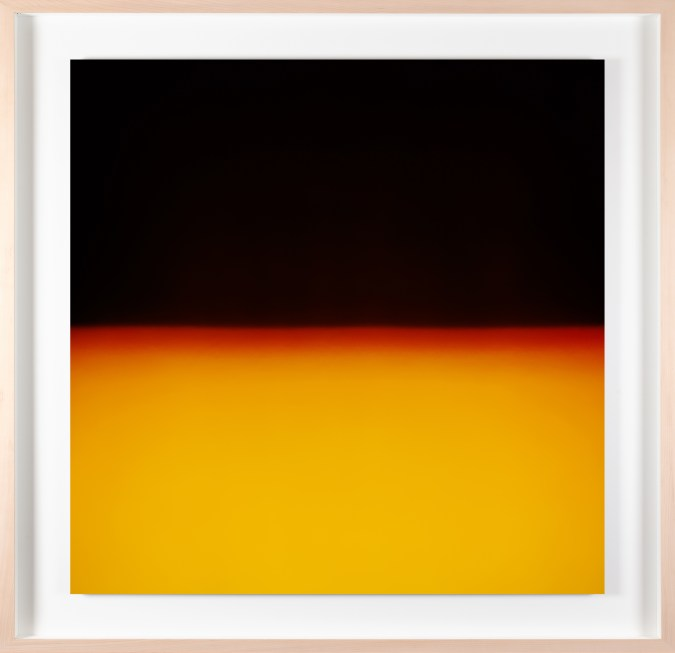 A framed photograph of a bright yellow-orange color field, with black in the top half.