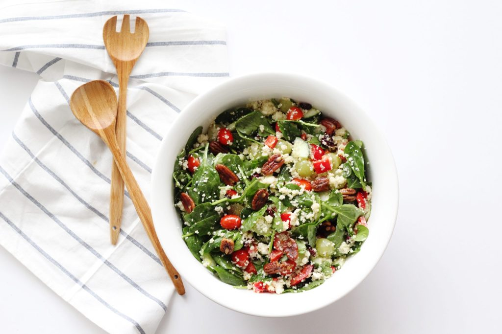 Kitchen Sink Salad in white bowl with wooden tongs