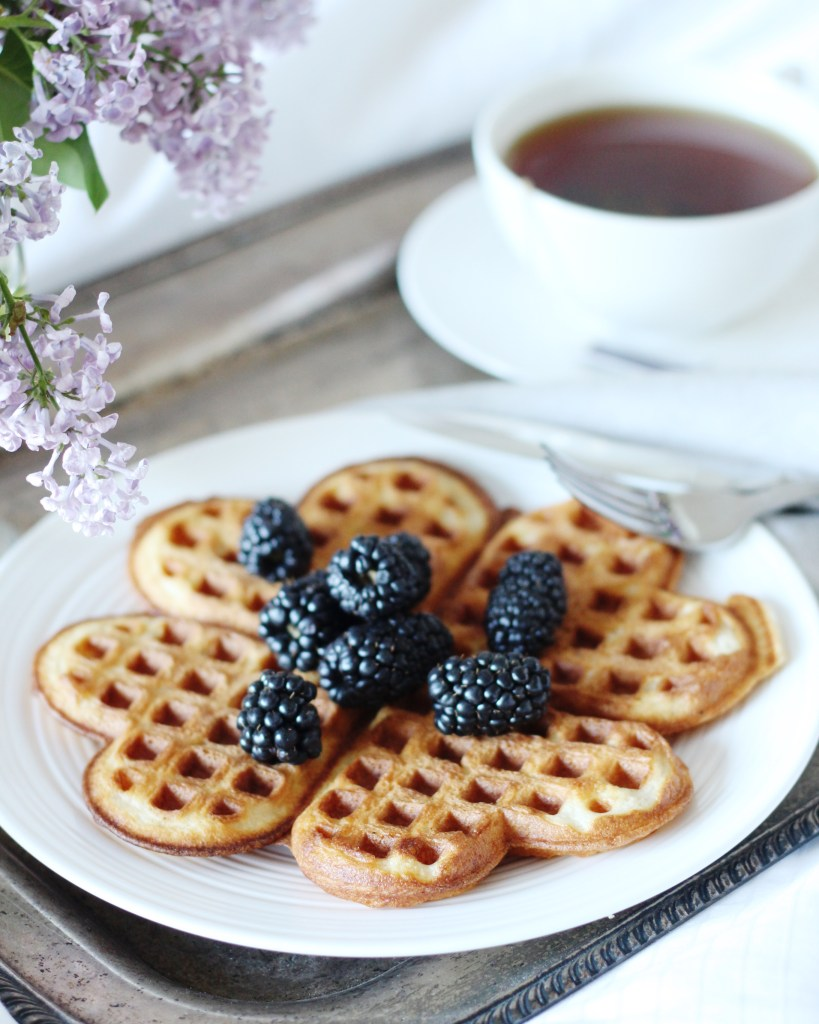 Vanilla Buttermilk Waffles topped with blackberries, cup of tea in white mug