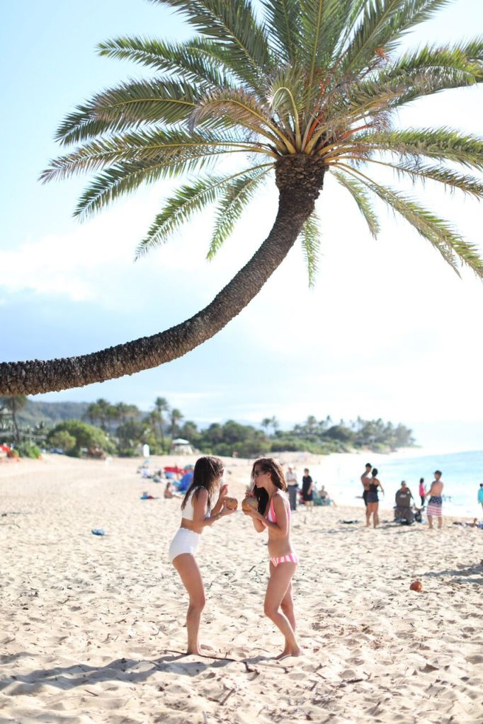 Tori Wesszer and Jillian Harris sip coconut water out of coconuts on the beaches of O'ahu!