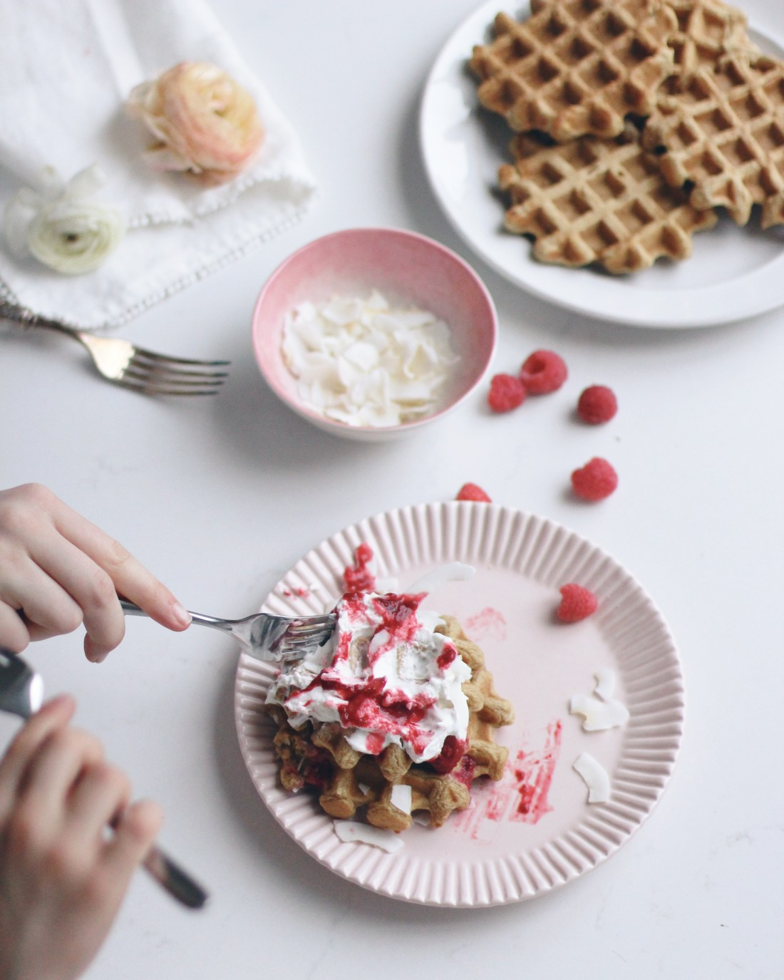 Messy pink plate of coconut waffles .