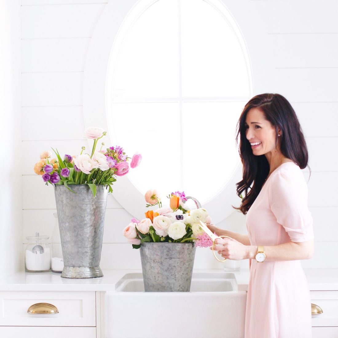 Spring flowers, pink dresses and oval window in a light white laundry room