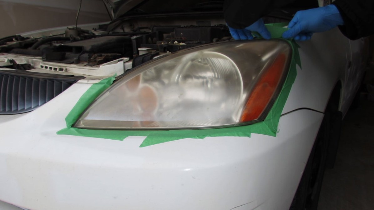 Mask off surrounding surfaces with painter's tape during headlight restoration