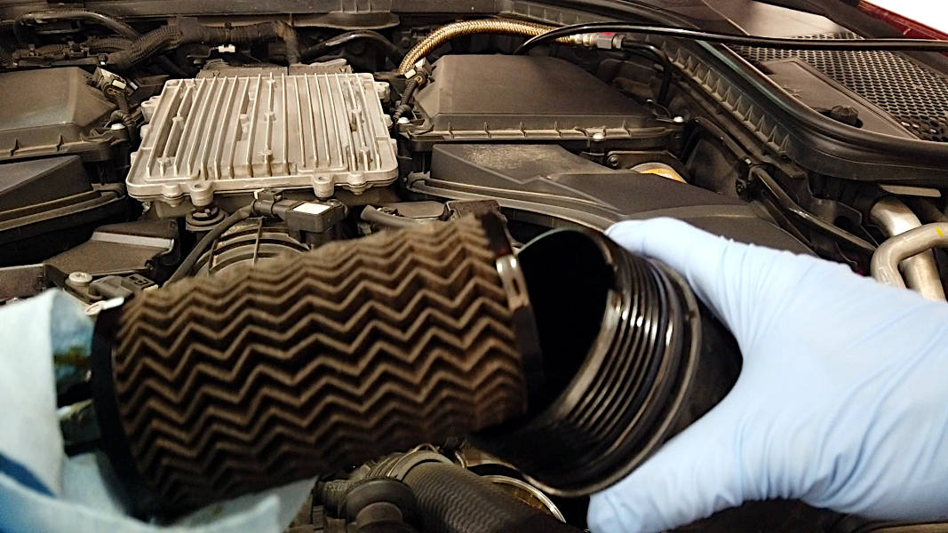 Removing the old oil filter element from the oil filter cap of a Mercedes-Benz C-Class
