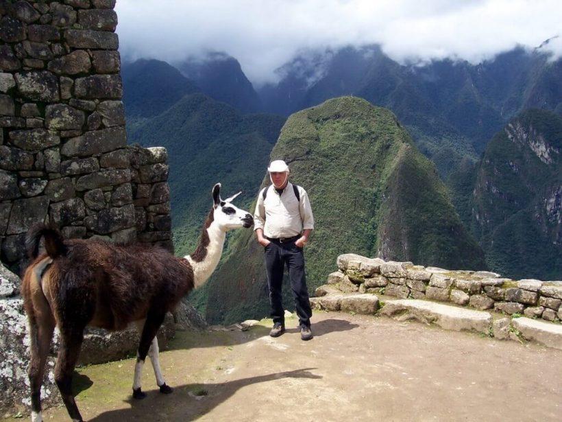 An image of Bob standing beside a Llama at Machu Picchu in Urubamba Province, Peru.