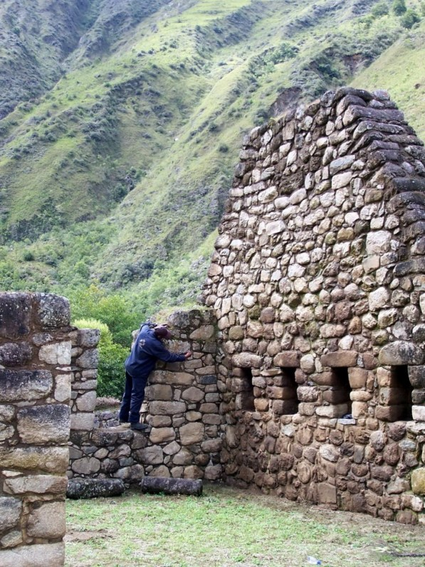 Worker repairs the stone walls at the Inca ruins at Chachabamba in Peru, South America