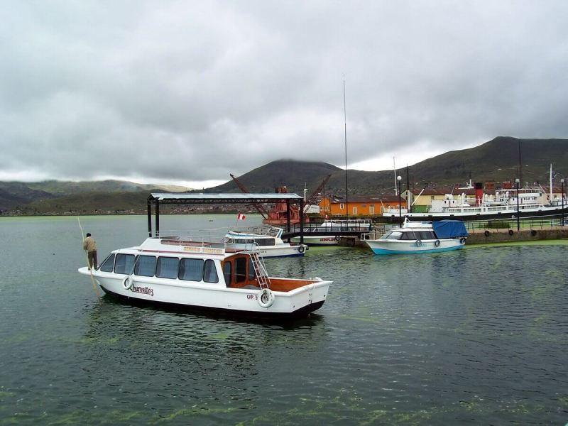 boat leaving puno harbour, lake titicaca, peru