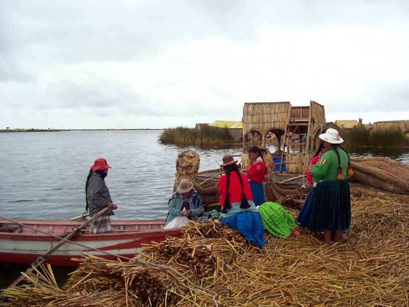 Uros woman buying food from a grocery boat on a floating island on Lake Titicaca in Peru, South America