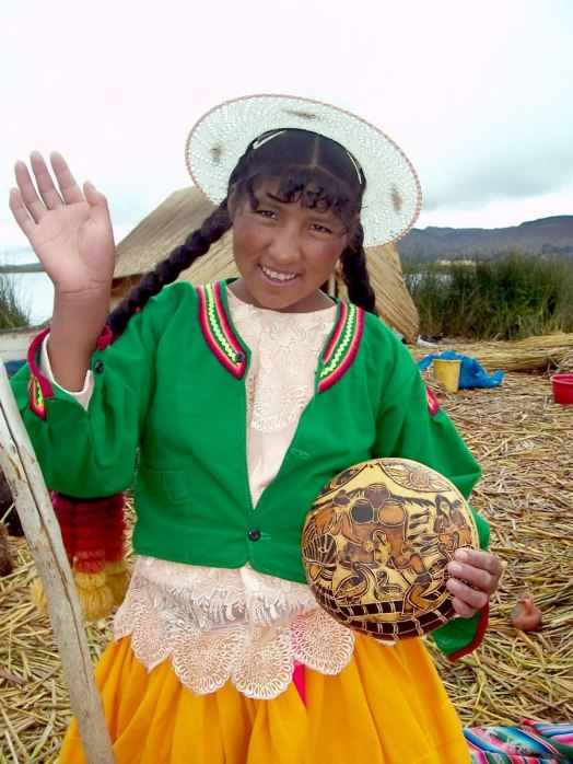 Uros girl waves good-bye from a floating island on Lake Titicaca in Peru, South America