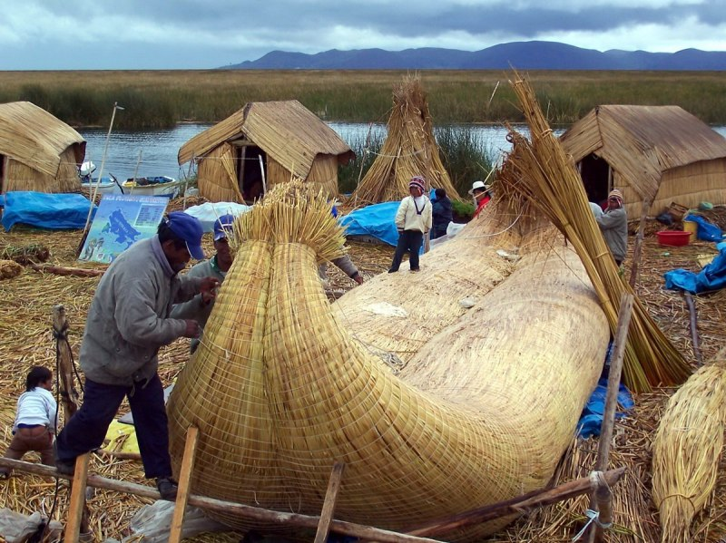 uros men construct reed boat, floating island, lake titicaca, peru