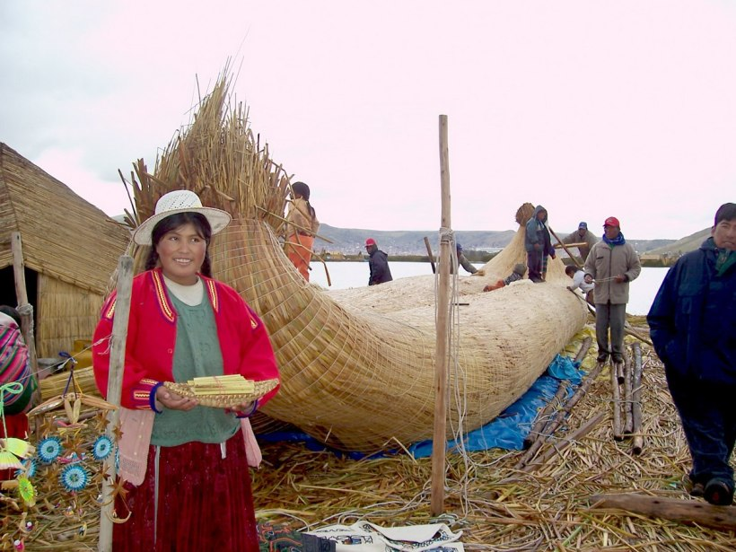 Uros men work on constructing a reed boat on a floating island on Lake Titicaca in Peru, South America