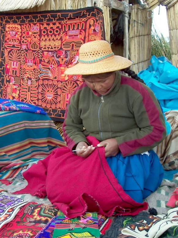 uros woman knits quilt, floating island, lake titicaca, peru