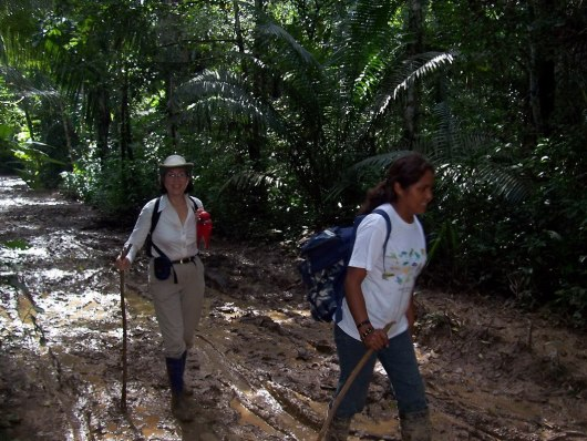 Jean follows Sonja along muddy Amazon pathway