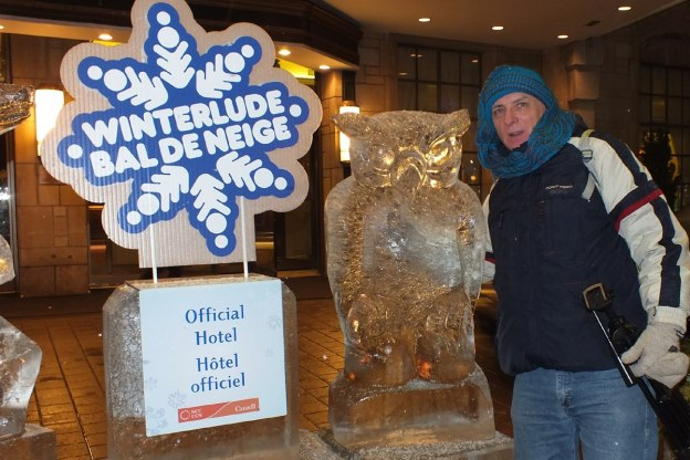 Bob stands beside ice sculptured Owl at Winterlude in Ottawa, Ontario, Canada