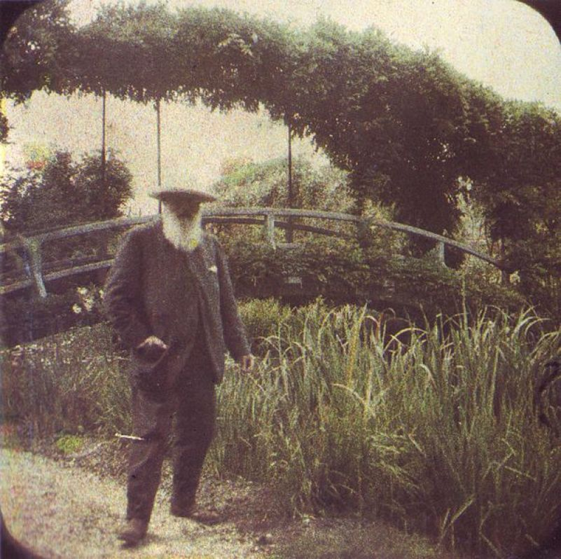 An image of Claude Monet standing beside the Water Lily Pond bridge in 1917, in Givenry, France.