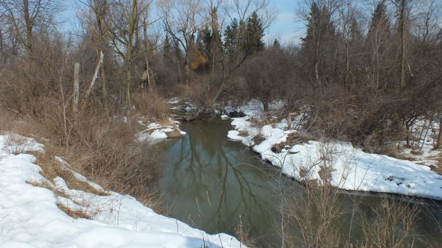 Water flows along snowy banks of a stream in the Claireville Conservation Area, in Toronto - Ontario