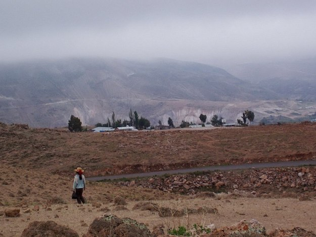 Young girl walks across the countryside near Nazca, Peru