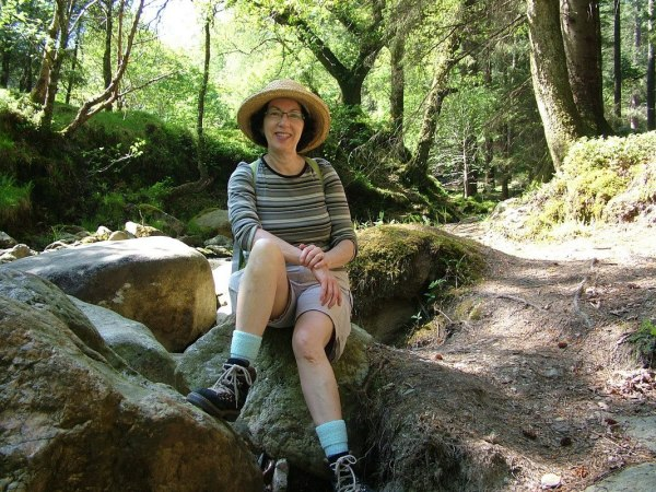 An image of Jean sitting near the Poulanass Waterfall in Wicklow Mountains National Park, County Wicklow, Ireland.  Photography by Frame To Frame - Bob and Jean.