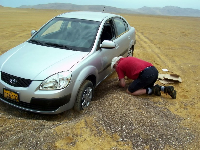 Digging car out of sand at Paracas National Reserve, Ica, Peru.