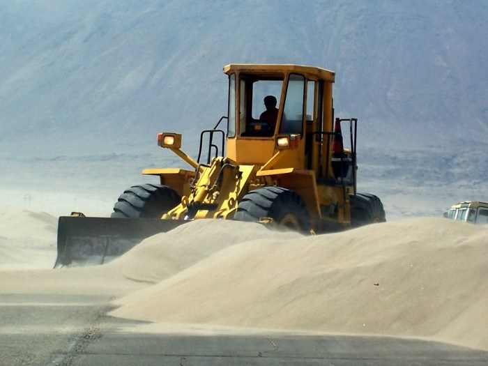 front end loader clears sand off pan american highway - peru