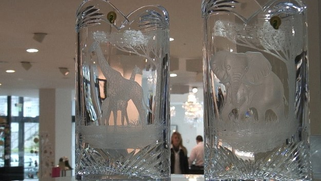 An image of two crystal vases with Elephants and Giraffe on them at House of Waterford Crystal in Waterford, Ireland. Photography by Frame To Frame - Bob and Jean.
