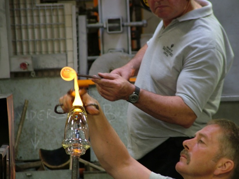 An image of glass blowers attaching molten glass to the base of crystal vase at the Waterford Crystal factory in Waterford, Ireland. Photography by Frame To Frame - Bob and Jean.