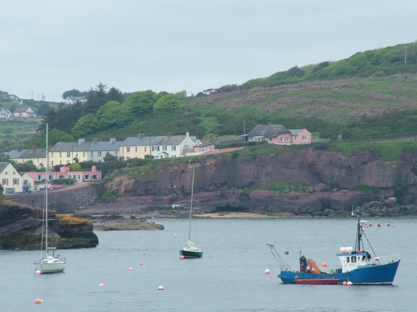 houses sitting along shoreline at dunmore east in county waterford - ireland