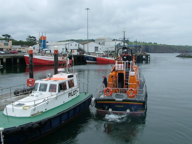 lifeboat and pilot boat leave dunmore east harbour in county waterford - ireland