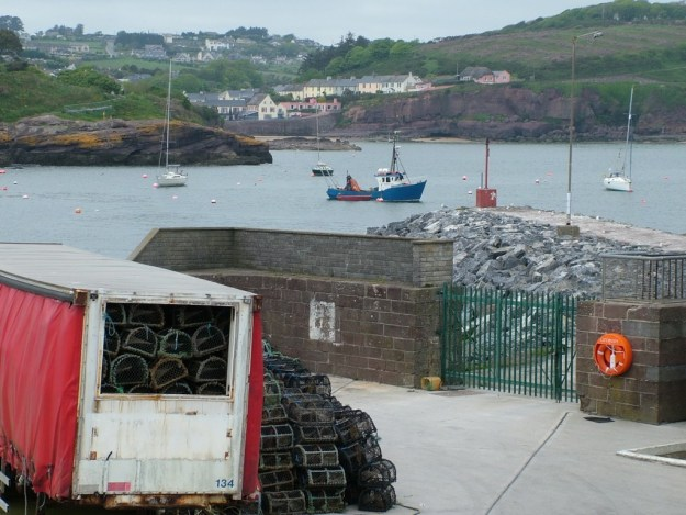an image of lobster traps sitting on main wharf at dunmore east in county waterford - ireland