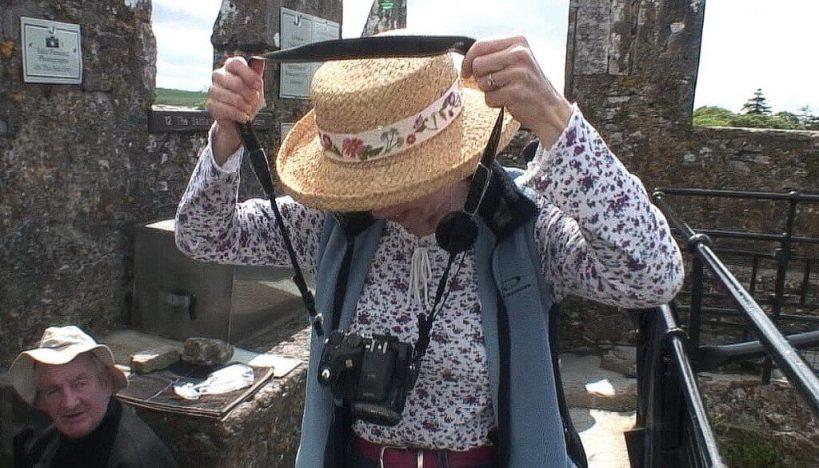 jean removes camera to kiss the blarney stone, blarney castle, ireland