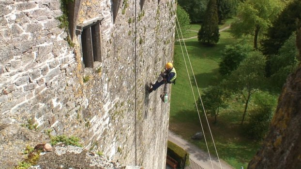 stone mason repairs outer wall of blarney castle, county cork, ireland