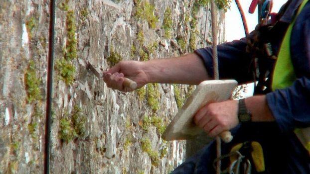 stone mason repairs wall of blarney castle with new mortar, ireland