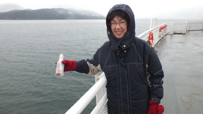 jean holds message in a bottle over side of BC ferry