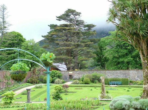 Tall trees and stone walls in the Walled Garden at Kylemore Abbey in County Galway, Ireland.