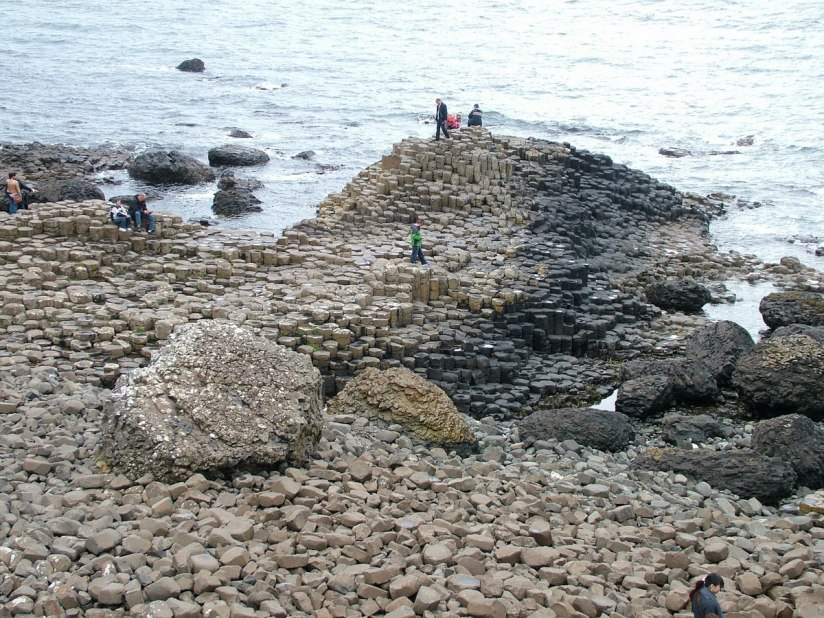 An image of people sitting and standing on the hexagonal columns at the Giant's Causeway, near Portrush, Northern Ireland. Photography by Frame To Frame - Bob and Jean.