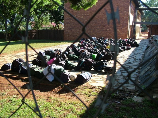 Children's backpacks behind razor wire in Sabie, South Africa