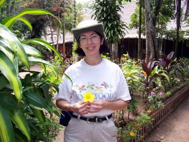 Jean holding yellow flower at Sandoval Lake lodge, Lake Sandoval, Amazon Basin, Peru