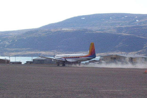 photograph of a First Air prop plane landing on the dirt runway in Pangnirtung on Baffin Island in Nunavut, Canada