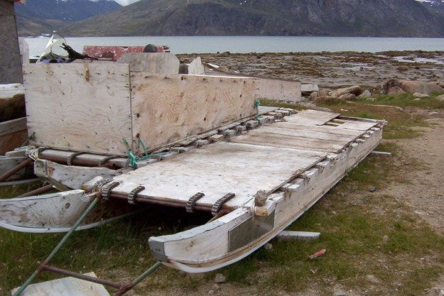 photograph of inuit toboggans sitting on the grass in Pangnirtung, Nunavut, Canada.