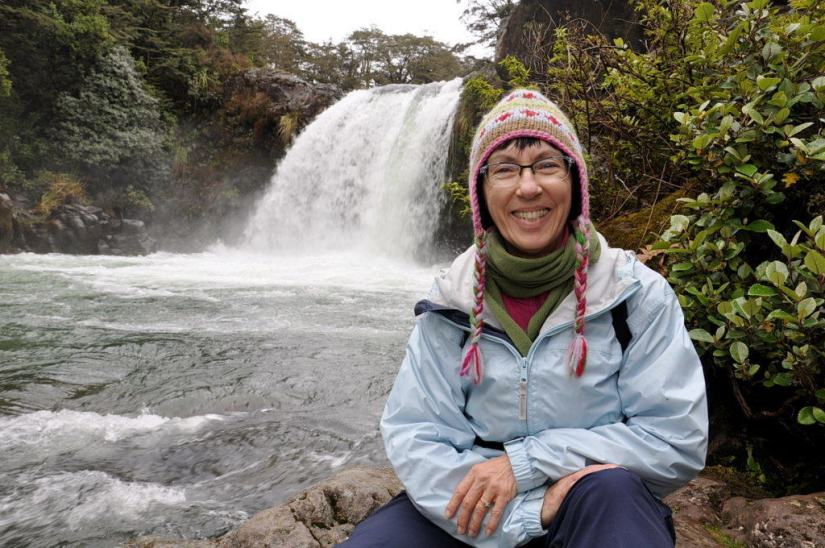 An image of Jean sitting on the rocks at Tawhai Falls in Tongariro National Park in New Zealand, where Gollum in Lord of Rings sat on the edge of Gollum's Pool. Photography by Frame To Frame - Bob and Jean.