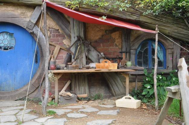 An image of various woodworking tools sitting on a bench in front of the carpenters hobbit hole at Hobbiton in New Zealand. Photography by Frame To Frame - Bob and Jean.