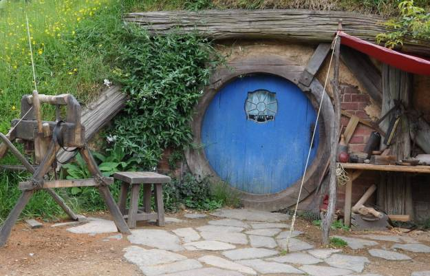 An image of the carpenters hobbit hole with a blue door at Hobbiton in New Zealand. Photography by Frame To Frame - Bob and Jean.