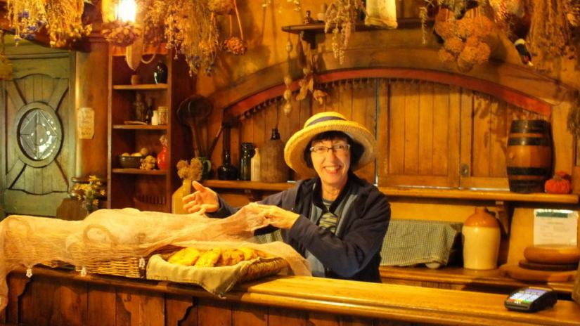 An image of Jean offering cookies for sale behind the main counter at the Green Dragon Pub at Hobbiton in New Zealand. Photography by Frame To Frame - Bob and Jean.