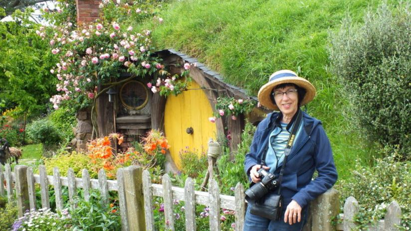An image of Jean standing in front of Sams House at Hobbiton in New Zealand. Photography by Frame To Frame - Bob and Jean.