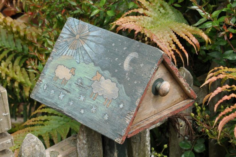 An image of a mail box with sheep painted on it at Hobbiton in New Zealand. Photography by Frame To Frame - Bob and Jean.