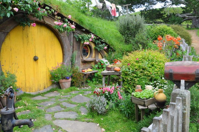 An image of Sams House with a yellow door and beautiful gardens at Hobbiton in New Zealand. Photography by Frame To Frame - Bob and Jean.