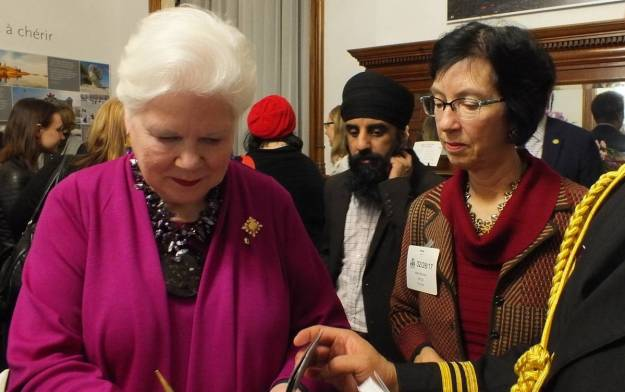 an image of the Honourable Elizabeth Dowdeswell signing a copy of the book 150 Stories, Toronto, Ontario, Canada