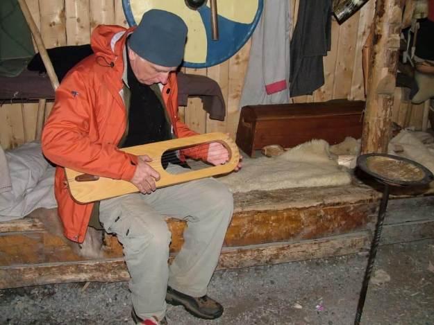 bob playing a viking harp at l'anse aux meadows, newfoundland, canada