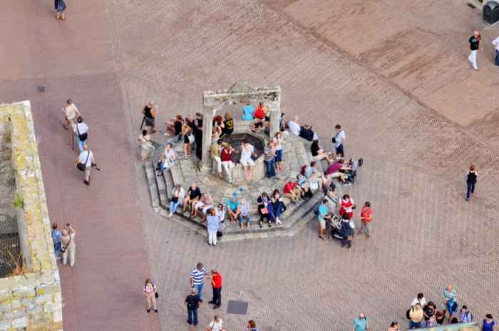 Image of tourists sitting at the drinking well in Piazza della Cisterna in San Gimignano, Italy.