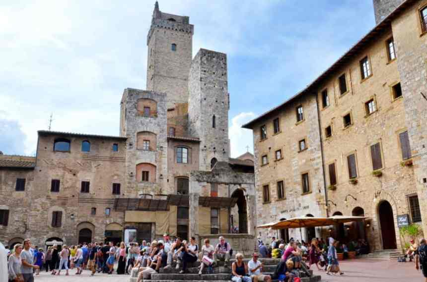 Image of tourists around the well and in Piazza della Cisterna, in San Gimignana, Italy.